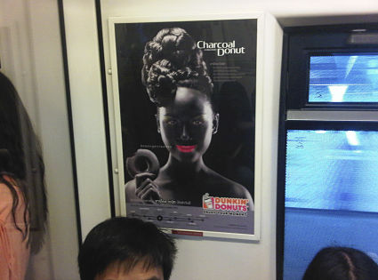 A Dunkin' Donuts advertisement showing a smiling woman with bright pink lips in blackface makeup is seen on a SkyTrain in Bangkok. Pic: AP.
