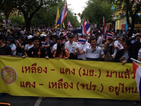 "Thammasat University students holding a protest banner: ""Yellow-Red (Thammasat) are here. Where are Red-Yellow (Military Cadet Academy)? (The colors here refer to institutional colors, not political colors.)"