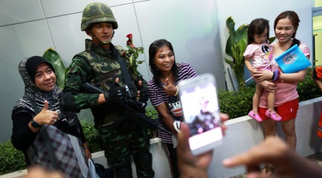 "A Thai soldier poses for photograph with Thai-Muslim women during an event called ""Return Happiness to Thai People"" in Bangkok, Thailand, Saturday, June 7, 2014. Thai police warned online critics of the military junta Friday that they will ""come get you"" for posting political views that could incite divisiveness, the latest reminder about surveillance of social media in post-coup Thailand. (AP Photo/Wason Wanichakorn)"